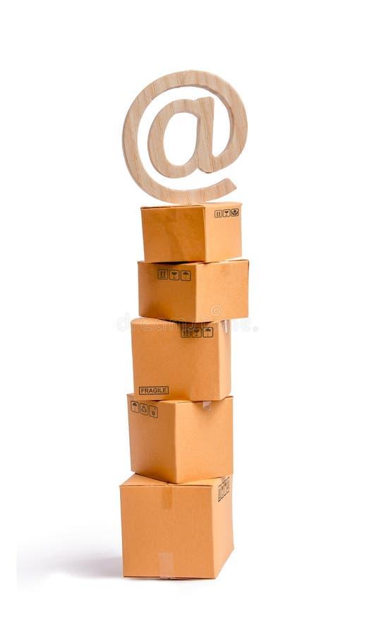 Een toren van kartondozen en een e-mailsymbool op bovenkant Het en online concept die online verkoop, winkelen winkelen totstandb stock foto