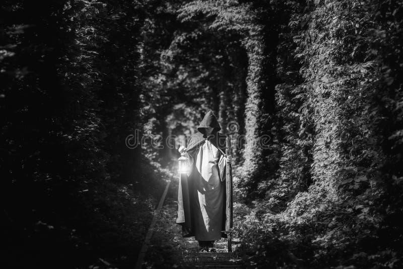 Een tovenaar in een mantel in een donker bos met een lantaarn Zwart-wit beeld stock fotografie