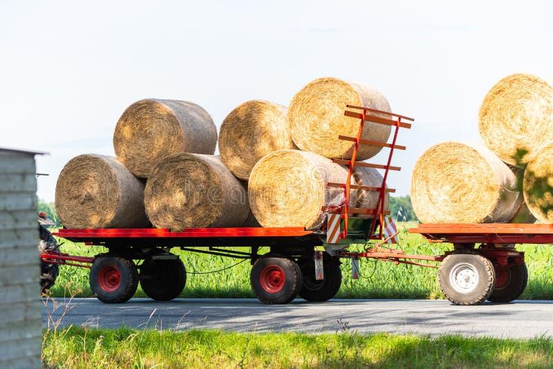 Een tractor drijft met twee aanhangwagens en sommige hooibalen op een landweg royalty-vrije stock fotografie