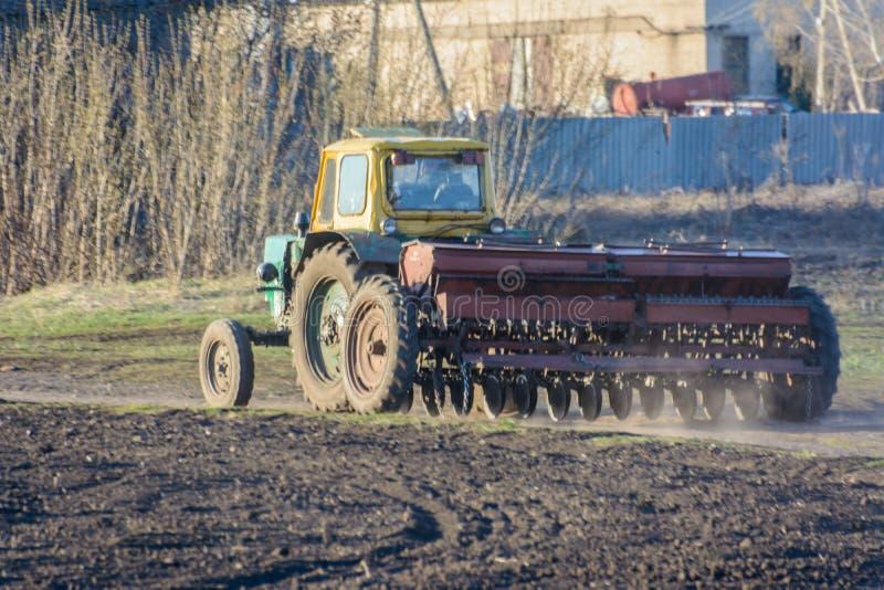 Een tractor met een landbouwer keert met een het zaaien campagne langs een landelijke weg terug De tractor blokkeerde volledig de royalty-vrije stock afbeeldingen