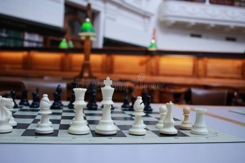 een traditioneel houten schaakbord dat op tafel ligt in een oude bibliotheek die wachtte op spelers om een stil spel te spelen stock foto