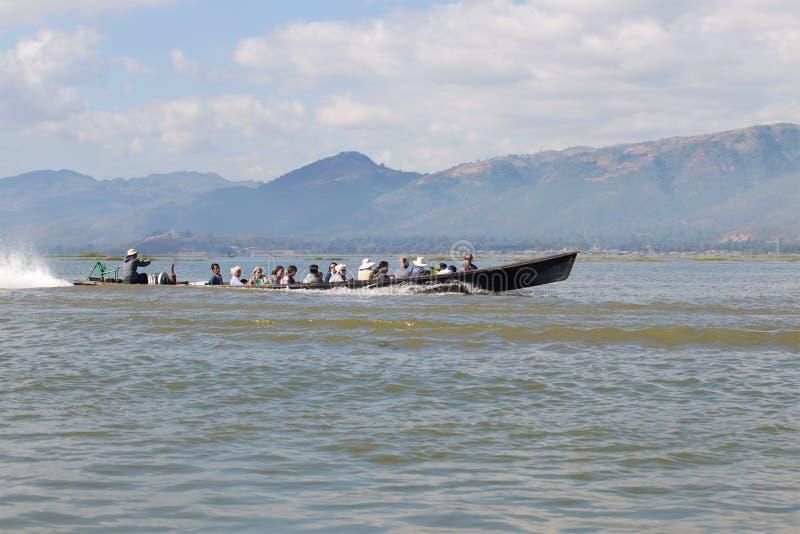 Een traditionele Birmaanse motorboot met plaatselijke bewoners zwemt op het meer royalty-vrije stock foto's