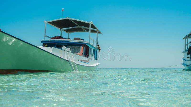 Een traditionele boot die verankerde op overzeese pijnlijke plek met ondiepe overzees met duidelijk en transparant water vissen royalty-vrije stock foto's