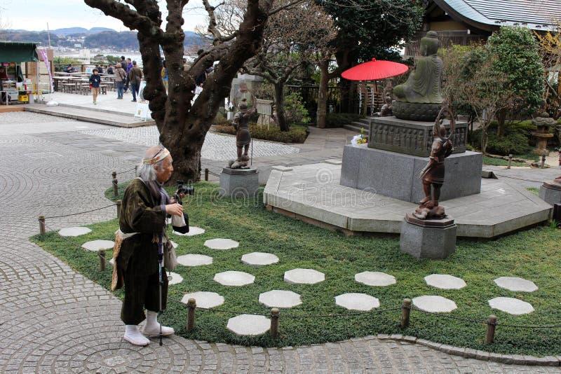 Een traditionele Japanse pelgrim? het nemen van foto's in Hasedera Tem stock foto's