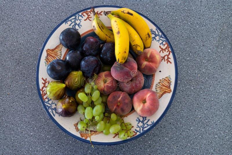 Een traditionele kleikom met heel wat verschillend de zomerfruit stock fotografie