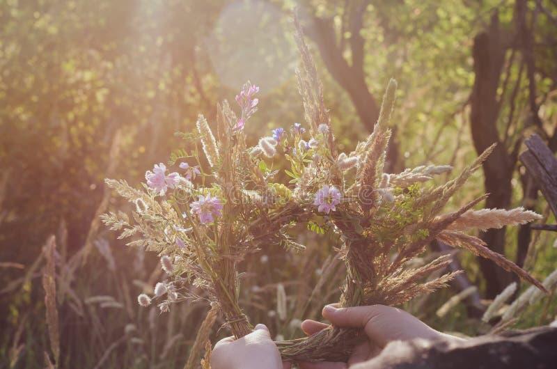 Een traditionele kroon van gebiedskruiden en bloemen in de handen van het meisje in de zon Het voorbereidingen treffen voor de ri stock foto