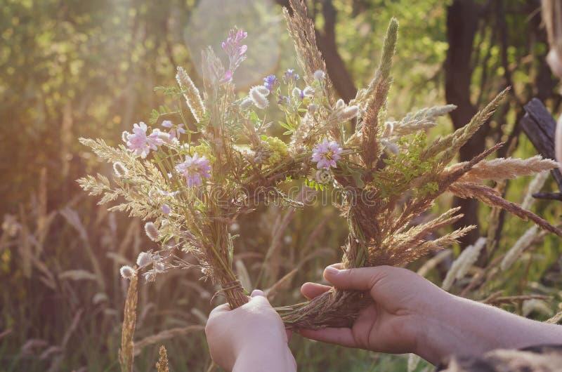 Een traditionele kroon van gebiedskruiden en bloemen in de handen van het meisje in de zon Het voorbereidingen treffen voor de ri stock fotografie
