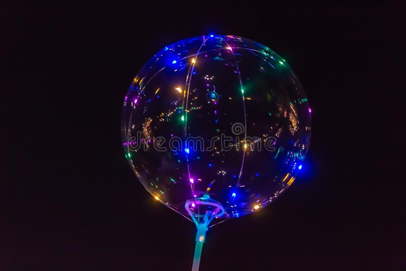 Een transparante ballon gloeit met lampen verschillende kleuren op zwarte royalty-vrije illustratie