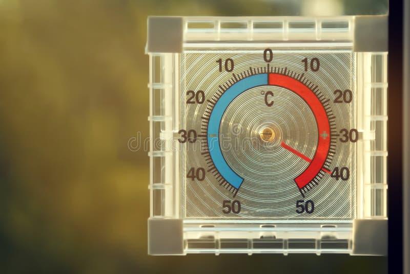 Een transparante vierkante thermometer toont op hoge temperatuur stock foto