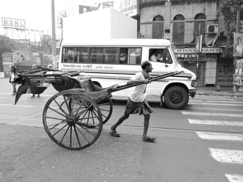 Een trekker van de handriksja trekt zijn riksja in het midden van de weg royalty-vrije stock afbeelding