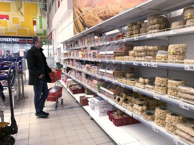 Een tribune met kruidenierswinkels, koekjes en cakes in Auchan-hypermarket stock foto's