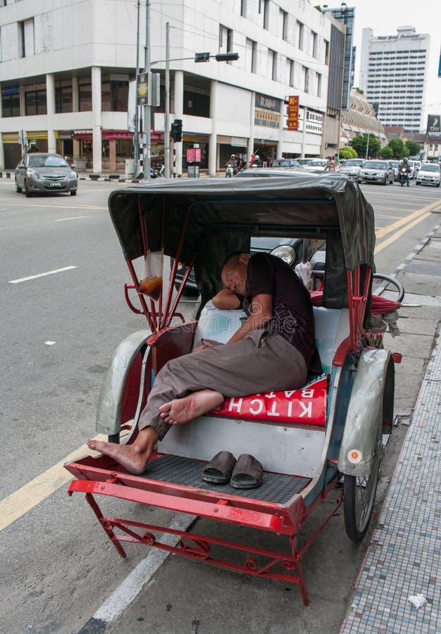 Een trishawbestuurder in George Town, Maleisië. stock foto's