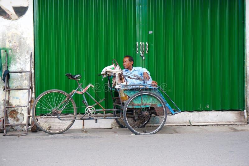 Een trishawruiter rust stock afbeelding