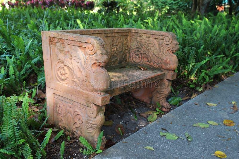 Een tuinbankje met mythologische beeldhouwkunst stock foto