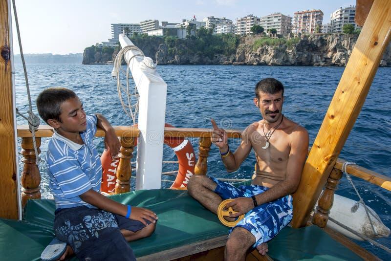 Een Turkse mens die van een cruiseboot vissen in Antalya-Baai in Turkije royalty-vrije stock afbeelding