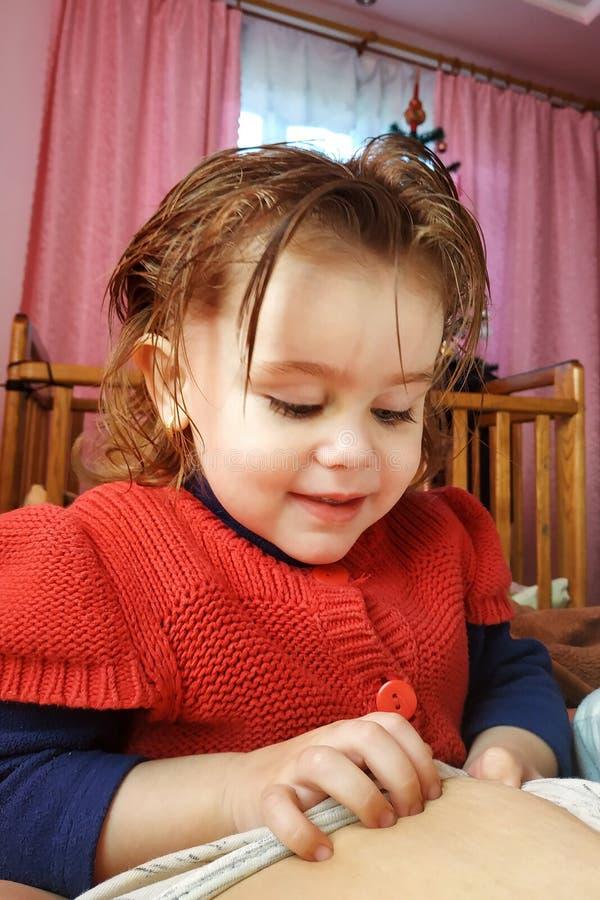 Een twee-jaar-oud meisje ligt op de moeder en drinkt moedermelk, de tijd van eenheid van moeder en kind stock foto's