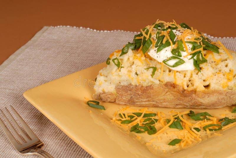 Een tweemaal aardappel in de schil met sjalotten, kaas en zure room stock foto