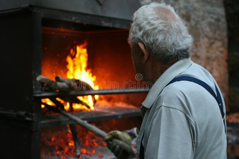 Een typisch Italiaans dorp De grijs-haired oude mens steekt een brand in de oven aan royalty-vrije stock afbeelding