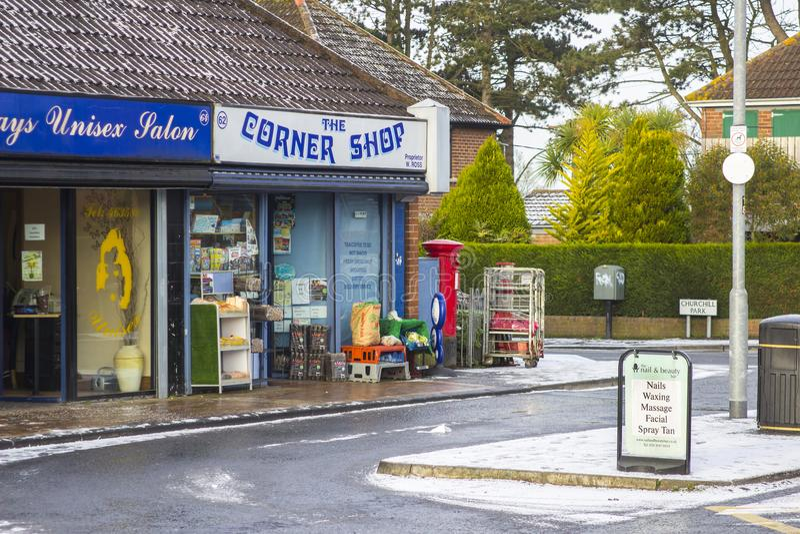 Een typische hoekwinkel en lokale schoonheidsspecialisten open voor zaken op een sombere de winterochtend op de Ballymaconnell-Ro stock afbeelding