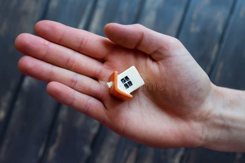 Een uiterst klein beeldje, een stuk speelgoed, een model van een huis ligt op open m stock afbeelding