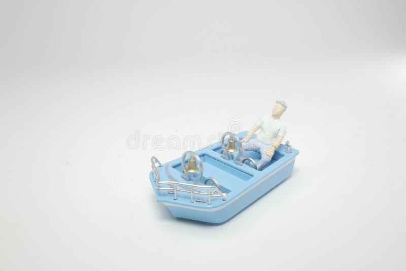 een uiterst klein cijfer met een kleine boot royalty-vrije stock afbeeldingen