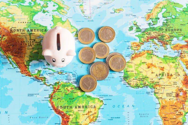 Een uiterst klein spaarvarken bevindt zich op een kleurrijke kaart van de wereld, Ne royalty-vrije stock foto