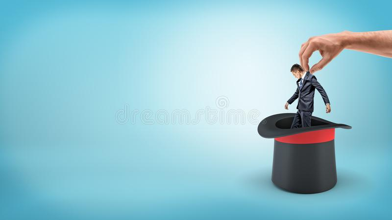 Een uiterst kleine zakenman op een blauwe achtergrond in genomen uit een illusionist` s hoed door een grote mannelijke hand royalty-vrije stock fotografie