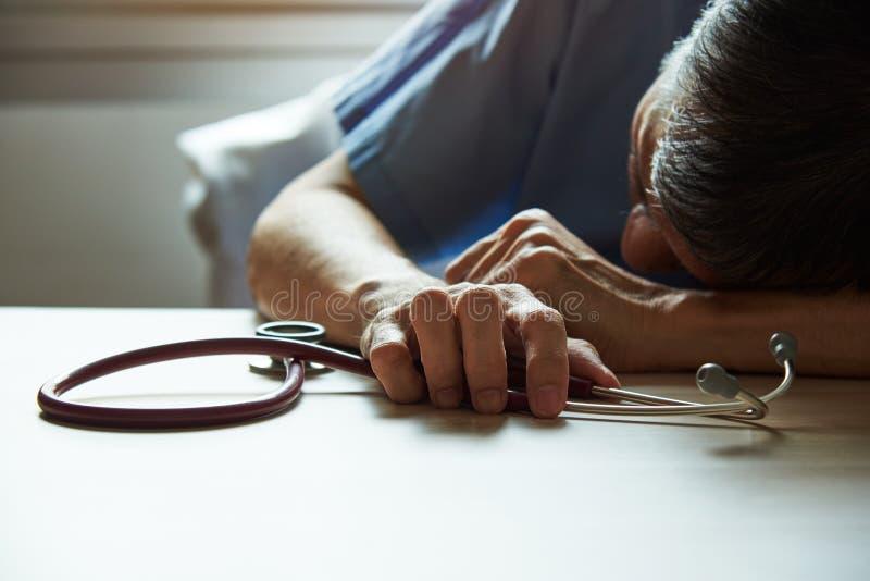 Een uitgebluste dokter die zich moe voelt in een medisch kantoor stock afbeeldingen