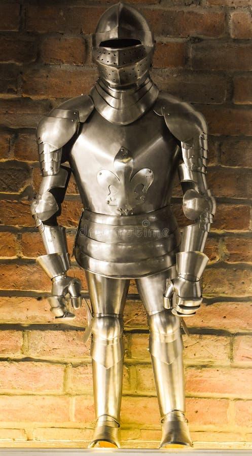 Een uitstekend Europees volledig kostuum van het lichaamspantser tegen de bakstenen muurachtergrond stock fotografie
