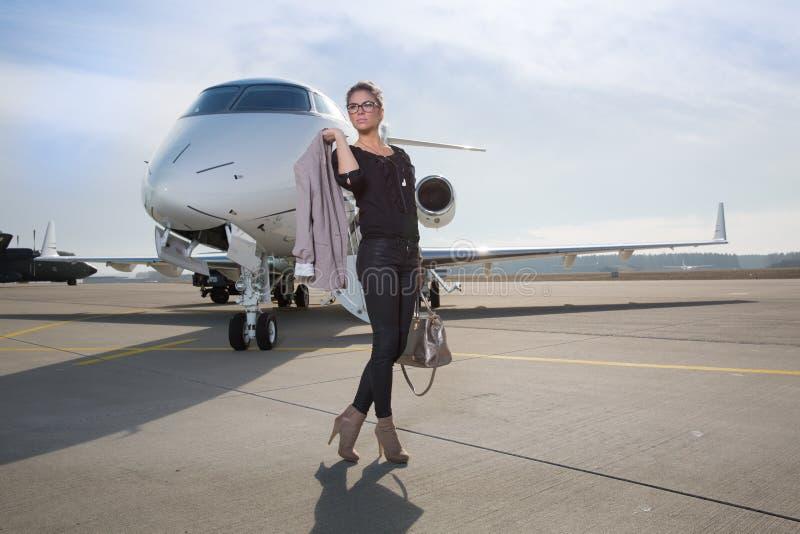 Een uitvoerende bedrijfsvrouw die een vliegtuig verlaten royalty-vrije stock afbeeldingen