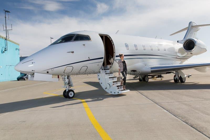 Een uitvoerende bedrijfsvrouw die een vliegtuig verlaten stock foto's