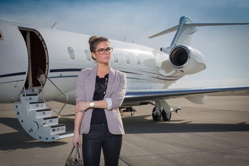 Een uitvoerende bedrijfsvrouw die een vliegtuig verlaten royalty-vrije stock foto's