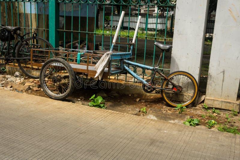 Een unieke vervoerscombinatie van kar en fiets parkeerde dichtbij groene omheining aan kant de binnen genomen straatfoto stock foto