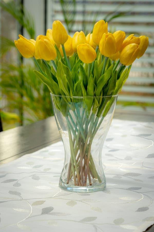 Een vaas met gele tulpen is op de lijst royalty-vrije stock afbeelding