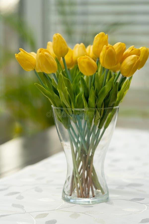 Een vaas met gele tulpen is op de lijst stock foto