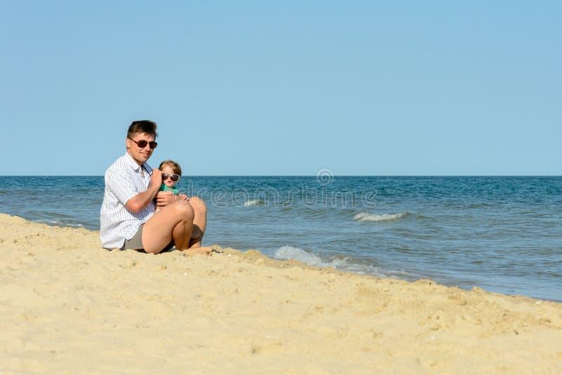 Een vader met een kleine dochter zit op het strand bij de achtergrond van het overzees royalty-vrije stock afbeelding