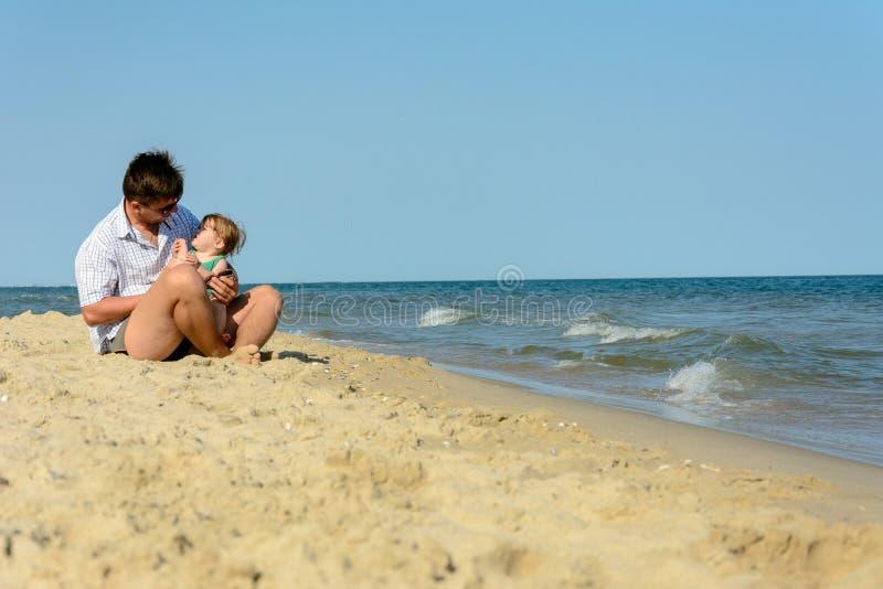 Een vader met een kleine dochter zit op het strand bij de achtergrond van het overzees royalty-vrije stock afbeeldingen