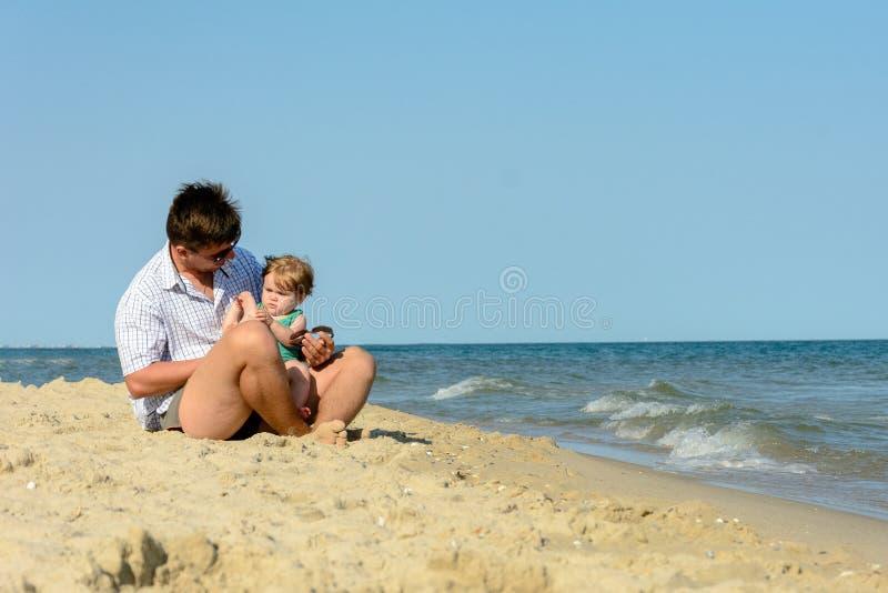 Een vader met een kleine dochter zit op het strand bij de achtergrond van het overzees royalty-vrije stock fotografie