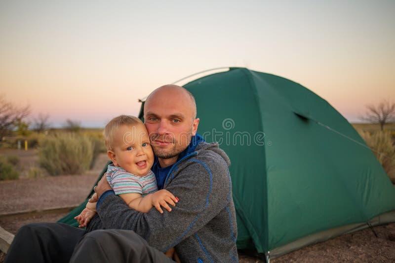Een vader speelt met zijn babyzoon bij de tent in kampeerterrein royalty-vrije stock foto