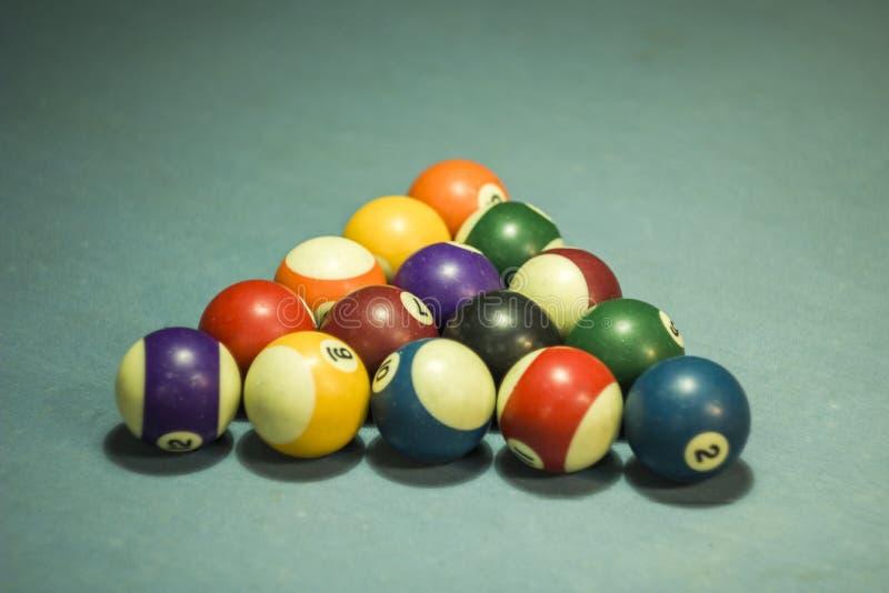 Een vage multi-colored biljartballen met aantallen op een blauwe doeklijst biljartballen in de piramide royalty-vrije stock foto