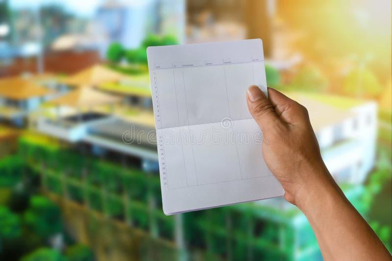 Een van de de besparingsrekening van de handholding de bankboek op architecturaal huis royalty-vrije stock foto's