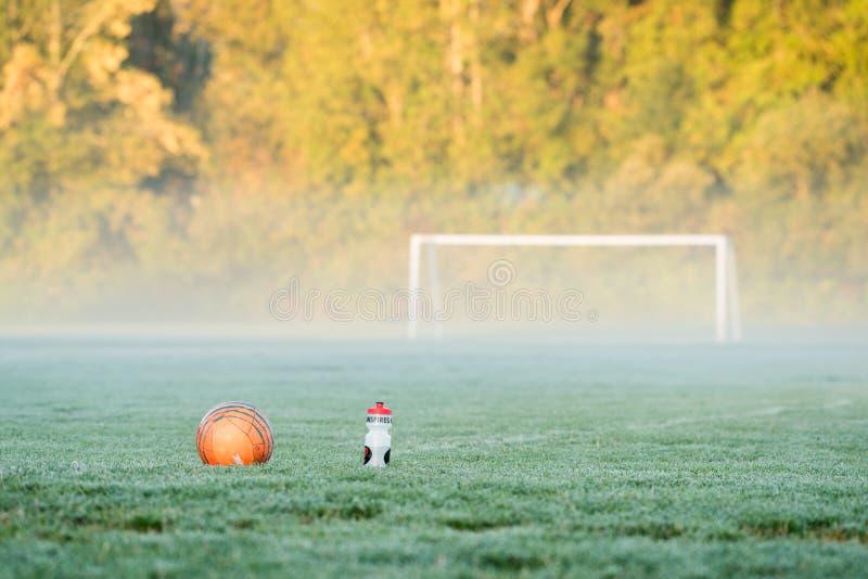 Een van het voetbalbal en water fles voor een voetbaldoel stock fotografie