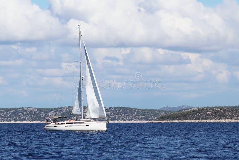 Een varend jacht wordt verankerd in een baai De mensen baden in het overzees Actieve rust op het Adriatische Overzees van het Med stock afbeelding