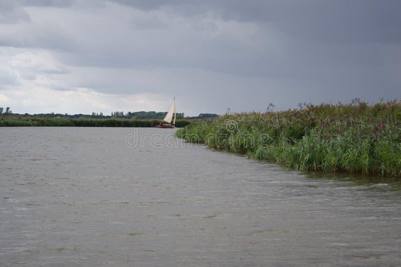 Een varende boot op een rivier in Norfolk Broads, vóór regen royalty-vrije stock fotografie