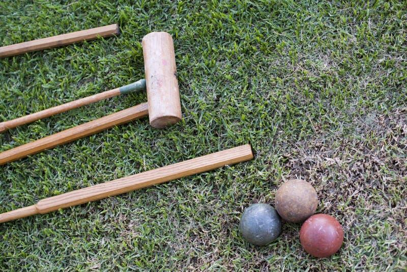 Een vastgesteld croquet ligt op een gazon van gras met drie ballen royalty-vrije stock fotografie