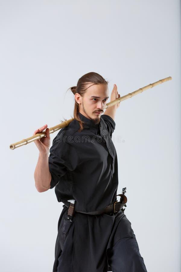 Een vechter, in het zwarte kimono stellen met een bamboe het vechten stok stock foto