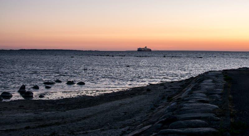 Een veerboot op de horizon bij zonsondergang royalty-vrije stock afbeeldingen