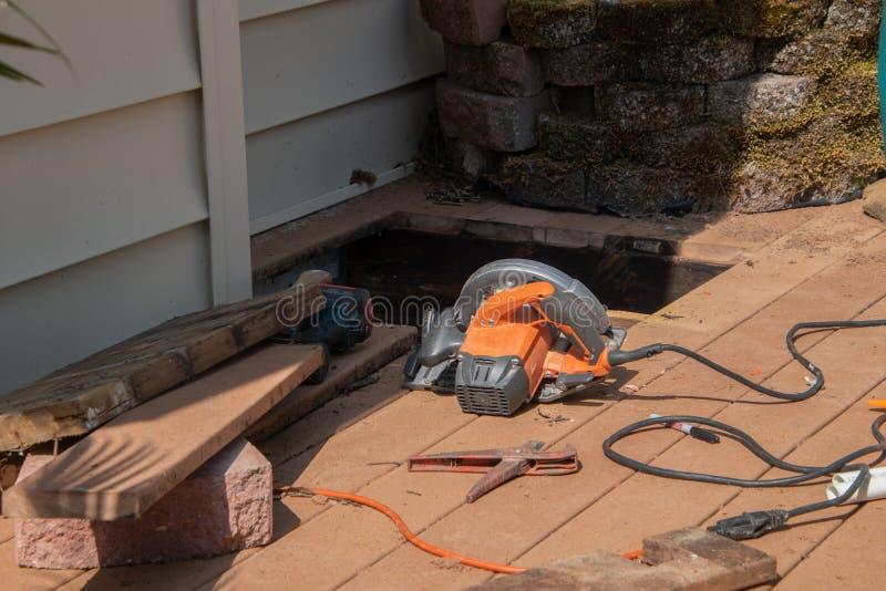 Een venster in bruin houten dek wordt gesneden een drainageprobleem onder het dek te herstellen dat Er zijn diverse machtshulpmid royalty-vrije stock afbeeldingen