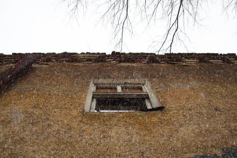Een venster in de muur van een oud geruïneerd huis stock afbeeldingen