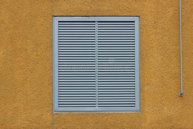Een venster in een groot industrieel winkelcentrum sloot met externe jaloezie in de vorm van ventilatietraliewerk geeloranje bei royalty-vrije stock foto